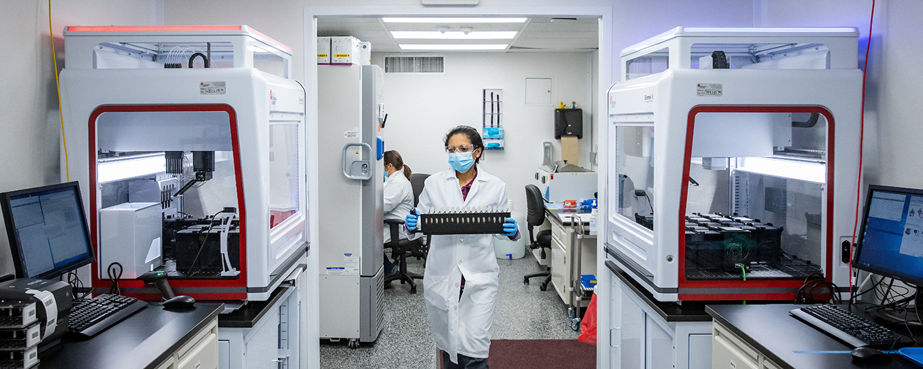 female researcher walking through lab with test samples