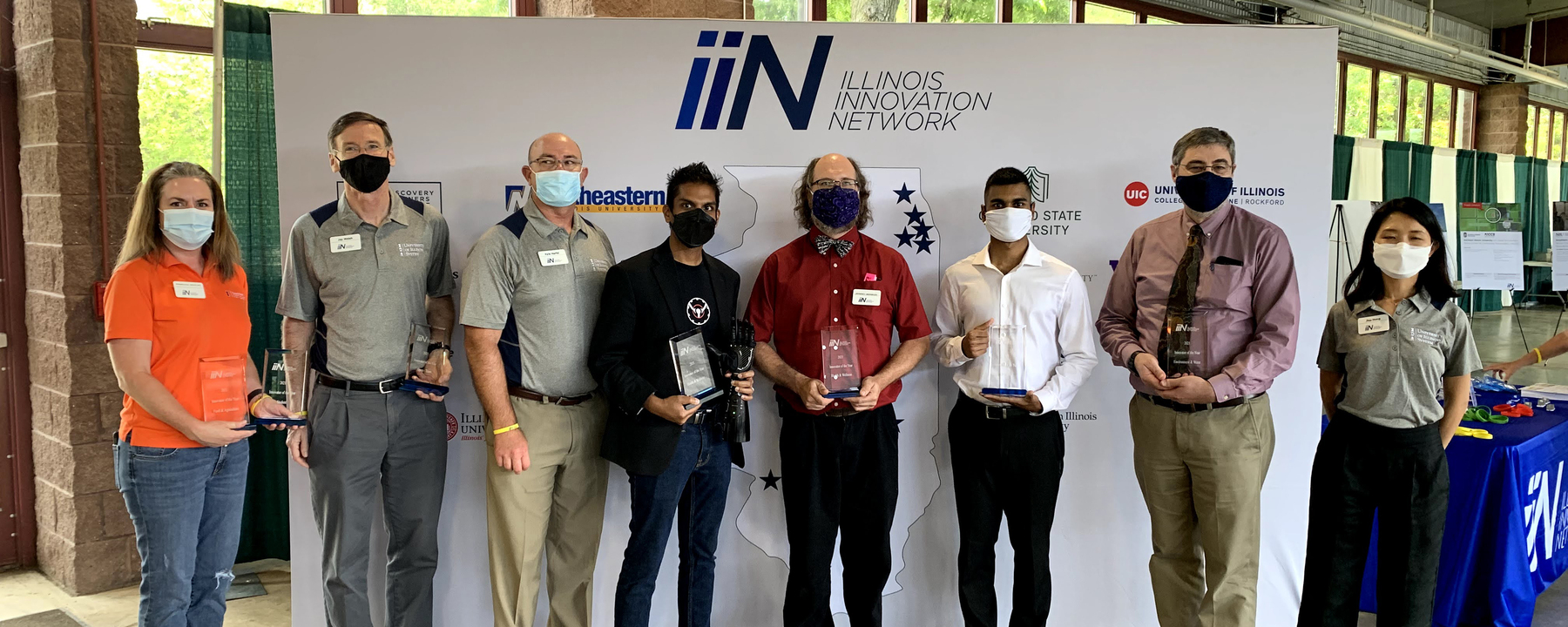 group of masked people holding awards in front of banner