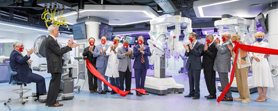 administrators in masks cut red ribbon in surgical center