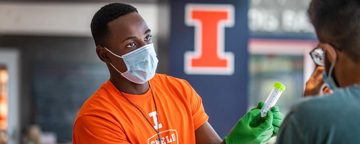 Masked Black male with orange SHIELD t-shirt h gloves handing test tube to man