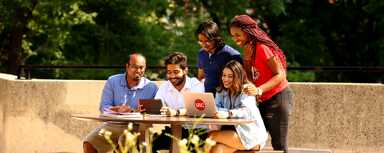 diverse group of students smiling grouped around table looking at UIC laptop
