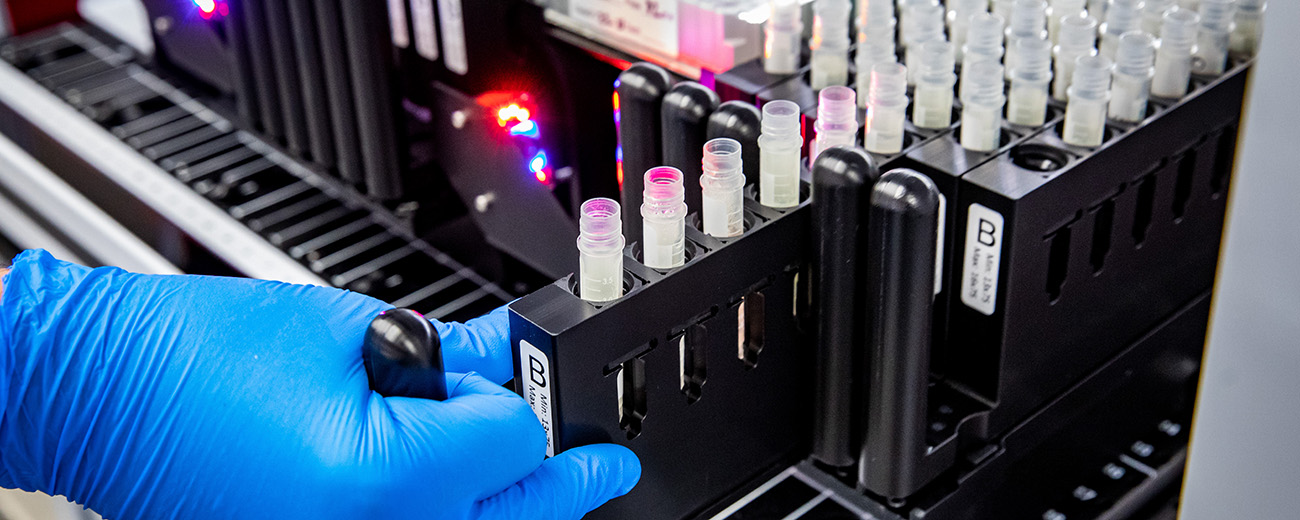 gloved hand and test tubes in lab