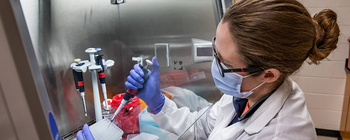 masked female researcher processing lab tests